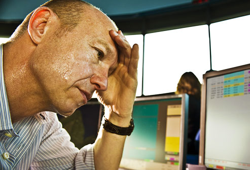 photolibrary_rm_photo_of_stressed_man_sweating_at_desk